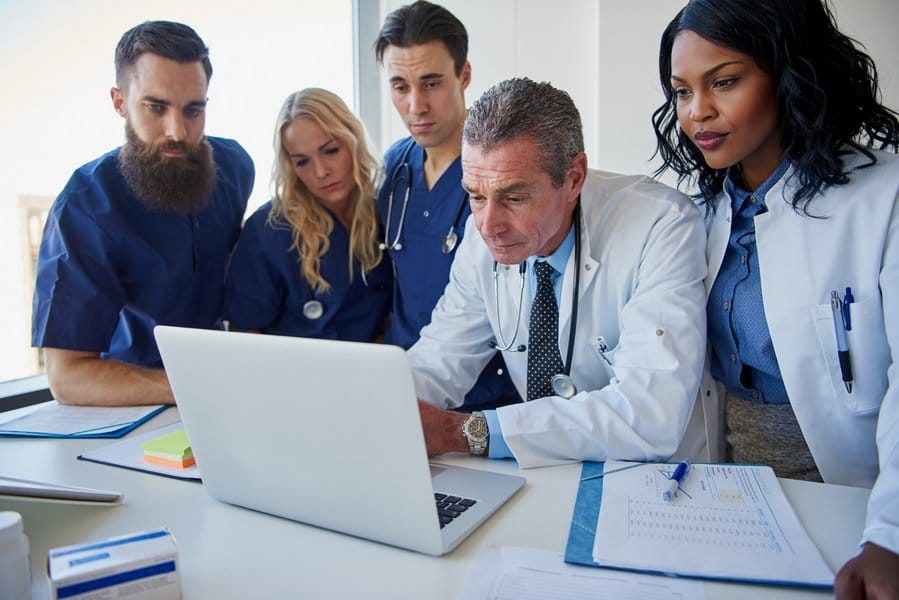 tn the medicine workers standing and browsing laptop HQRZSN5